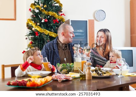 happy family near Christmas tree over celebratory table at home interior