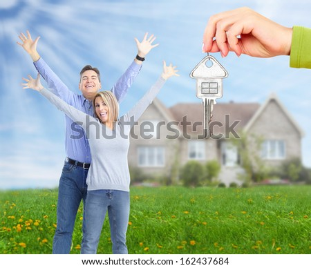 Happy family near new home. Real estate background. - stock photo