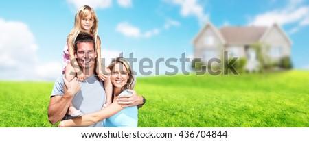 Happy family near new house. - stock photo