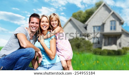 Happy family near new house. Real estate background. - stock photo