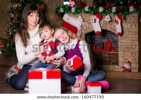 Happy family near the Christmas tree opening gifts.  smile.