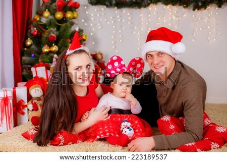 happy family near the Christmas tree. Red concept shooting, christmas