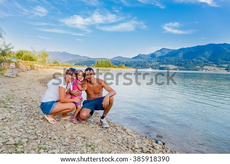 Happy family next to a mountain lake hiking and having fun.