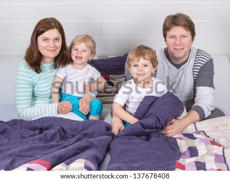 Happy family of a four having fun in pajamas at home in bed. - stock photo