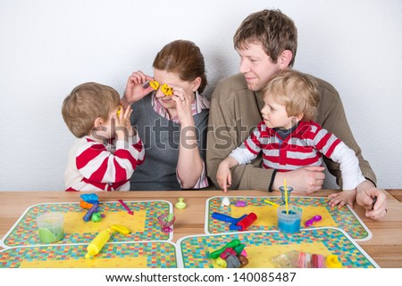 Happy family of a four having fun with modeling clay at home