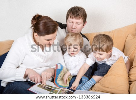 Happy family of a four watching old photos at home. In blue jeans and white shirts