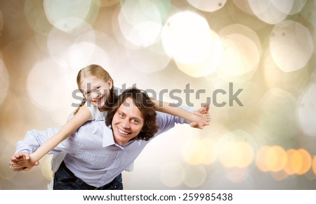 Happy family of father and daughter against bokeh background - stock photo