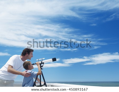 happy family of father and his son using seaside binoculars or telescope together