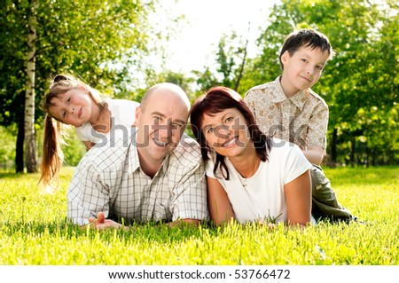 happy family of father and mother and their kids: brother and sister, on grass in park. All smiling and looking in camera