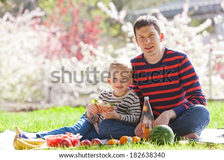 happy family of father and son having picnic together - stock photo