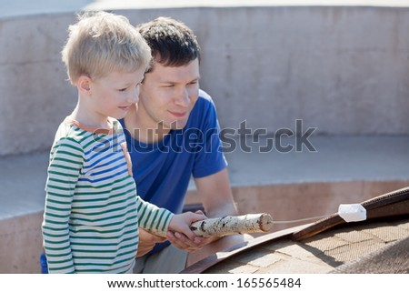 happy family of father and son making marshmallows - stock photo