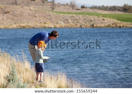 happy family of father and son making marshmallows, child in focus - stock photo
