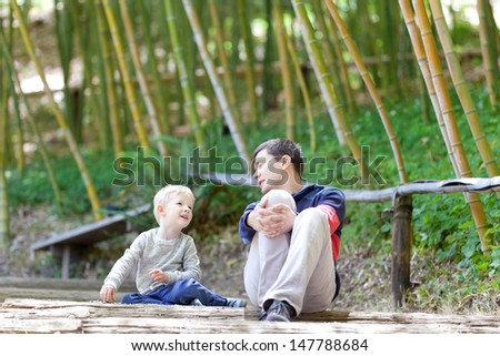 happy family of father and son talking together at japanese garden - stock photo