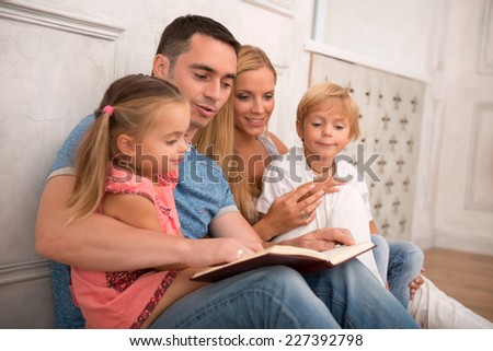 Happy family of father mother son and daughter smiling  looking  at camera sitting reading book   isolated on white background with copy place - stock photo
