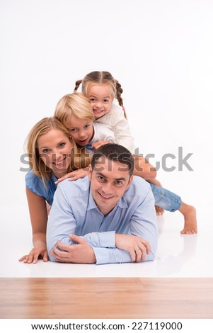Happy family of father mother son and daughter smiling  lying on each other   looking  at camera  isolated on white background