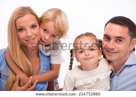 Happy family of father mother son and daughter smiling  squatting looking  at camera  isolated on white background waist up  - stock photo