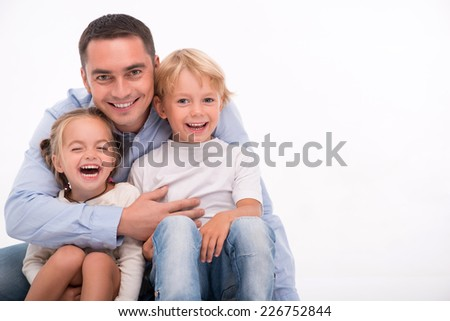 Happy family of father  son and daughter smiling  embracing  looking  at camera  isolated on white background with copy place - stock photo