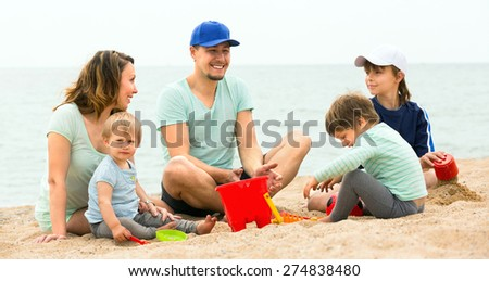 Happy family of five  spending a weekend in the summer on the beach - stock photo