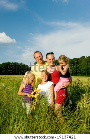 Happy family of five standing in the grass with and flowers together - metaphor for love - stock photo