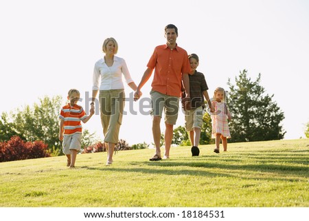 Happy family of five walking down a grassy hill