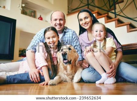 Happy family of four and their dog sitting on the floor at home - stock photo