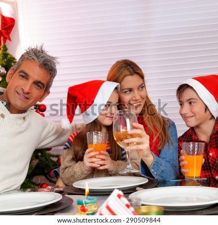 Happy family of four at Christmas table. - stock photo