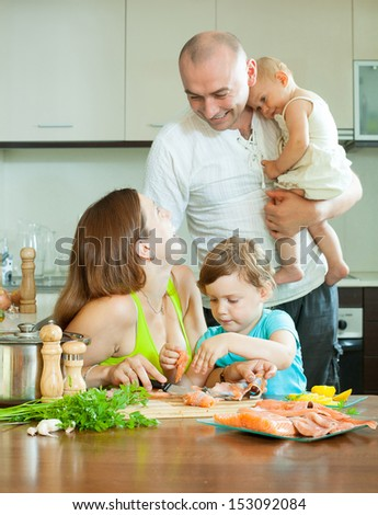 Happy family of four cooking salmon fish at home kitchen