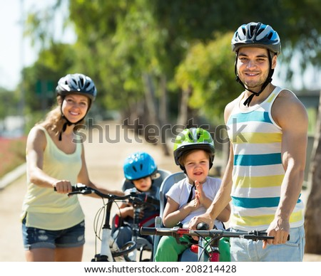 Happy family of four cycling on street road in summer day
