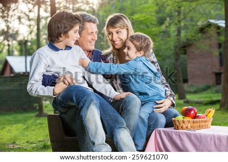 Happy family of four enjoying picnic in park - stock photo