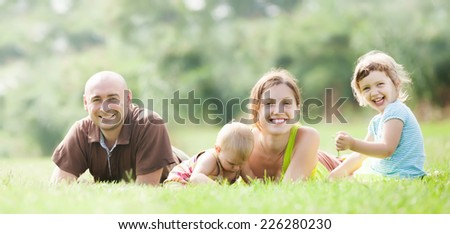 Happy family of four enjoying time at park in summer  - stock photo