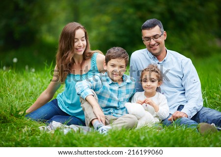 Happy family of four enjoying weekend in the park