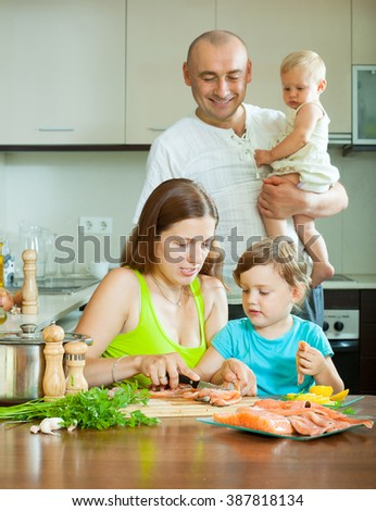 Happy family of four fish cooking at home kitchen  - stock photo