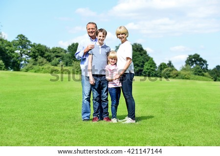 Happy family of four having nice time in summer park - stock photo