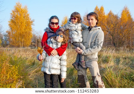 Happy family of four in autumn park, parents with kids having fun outdoors. Family weekend with children at autumn fall