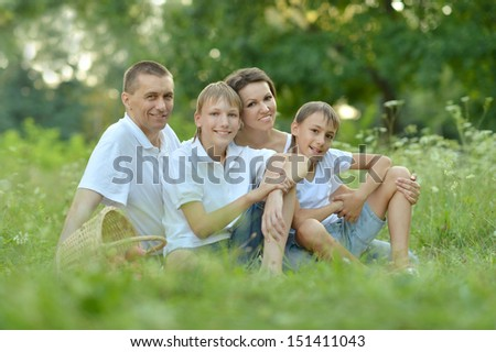 happy Family of four is having picnic in green summer park