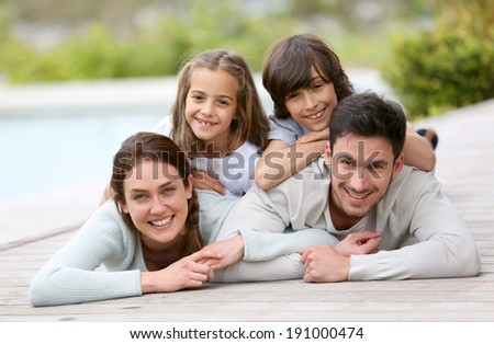 Happy family of four laying by the pool - stock photo