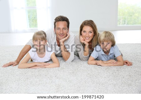 Happy family of four laying on carpet at home - stock photo