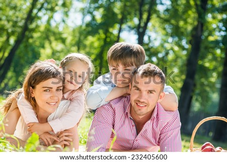 Happy family of four lying in summer park - stock photo