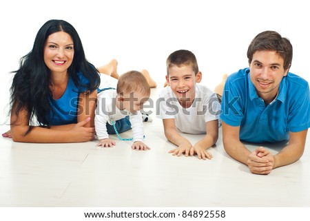 Happy family of four members lying on floor together and smiling against white background - stock photo