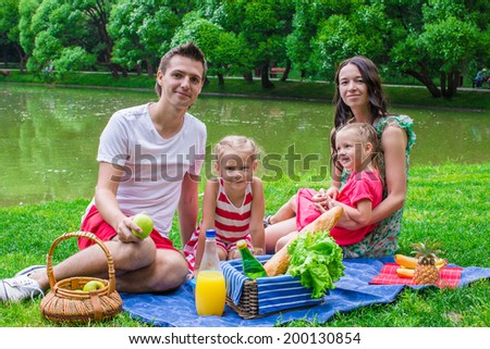 Happy family of four picnicking in the park on summer day