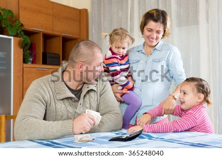 Happy family of four planning budget and smiling at home. Focus on man - stock photo