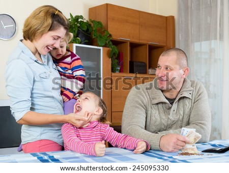 Happy family of four planning budget and smiling indoors. Focus on man - stock photo