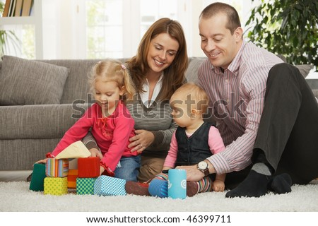 Happy family of four playing on floor  in living room sitting on floor in front of sofa.