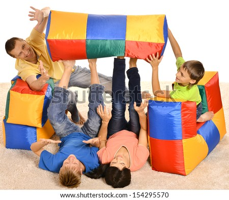 Happy family of four playing with colored cushions