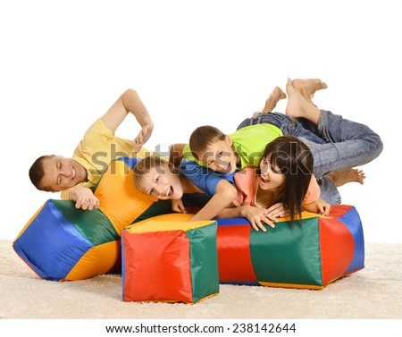 Happy family of four playing with colored cushions - stock photo