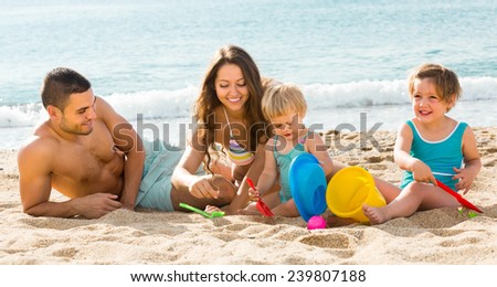 Happy family of four playing with sand at beach - stock photo