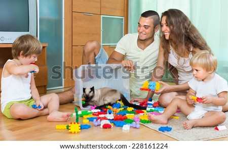 Happy family of four plays with meccano set in home. Focus on girl - stock photo