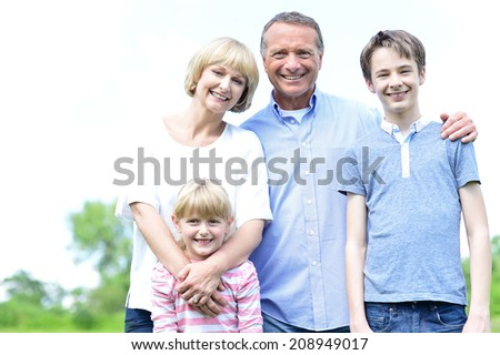 Happy family of four posing together in park