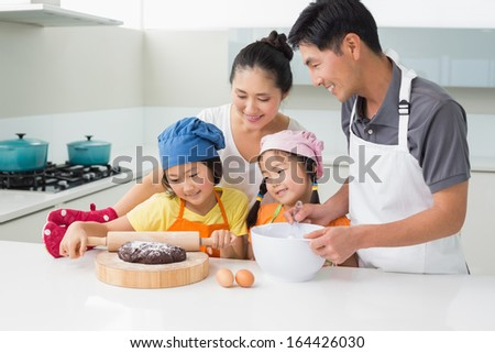 Happy family of four preparing cookies in the kitchen at home