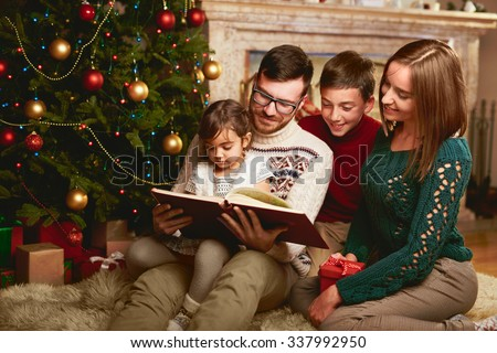Happy family of four reading together on Christmas evening